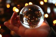 A christmastree through a crystal ball. A small hand with a crystal ball. You can see a christmastree upsidedown Stock Photos