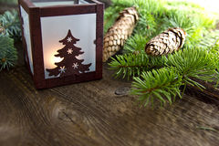 Christms decoration with lantern. Decorative metal lantern with christmas tree lit by a glowing candle with copy space Stock Image