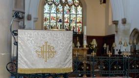 Christogram他的在讲坛布料在哥特式英国教会里 免版税库存照片