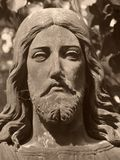 Christus face on grave in old abadoned cemetary, Detail of statue. Nice sculpture close-up, sepia-tinted photos royalty free stock images