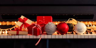 Chritmas balls and gift boxes on piano keyboard, front view. Chritmas balls and gift boxes on classical piano keyboard, front view royalty free stock image