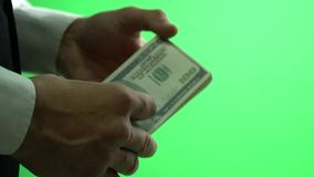 On the Chroma key businessman picks a hundred dollar bills in his hands. Hands of a businessman touching a bundle of one hundred dollar bills stock video