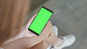 Chroma zeer belangrijk model met het groene scherm op mobiele telefoon van jonge vrouw thuis stock video