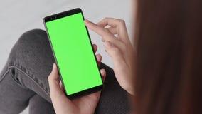 Chroma zeer belangrijk model met het groene scherm op mobiele telefoon van jonge vrouw thuis stock videobeelden