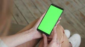Chroma zeer belangrijk model met het groene scherm op mobiele telefoon van jonge vrouw thuis stock footage