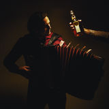 Chromatic Accordion Player And Bottle of Spirit Drink Stock Photography