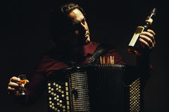 The chromatic accordion player with a spirit drink. stock photography