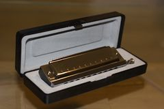 Chromatic harmonica in box. Chromatic harmonica in the box, wind-tongued tongue musical instrument, lips and tongue used for jazz, blues, country, folk, blues Royalty Free Stock Photo