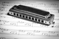 Chromatic Harmonica on Music Sheets. Black & White. Old Chromatic Harmonica on Music Sheets in Black & White Royalty Free Stock Photos