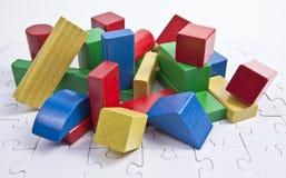 Chromatische Ziegelsteine auf einem weißen Puzzlespiel lizenzfreie stockfotografie