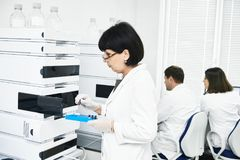 Chromatography. Researcher putting flask in equipment. Chromatography system at pharmaceutical laboratory. Female scientific researcher putting flask with liquid Royalty Free Stock Photo