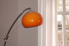 Chrome arc lamp from the 70s with orange plastic lampshade. In front of a window royalty free stock image