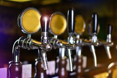Chrome beere faucets on a bar. Chrome beer faucets in a beer house. Beer bar background royalty free stock photography