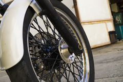 Chrome bike wheel. Near the garage Stock Photos