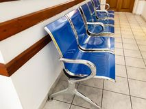Chrome and blue empty plastic seats on hospital corridor royalty free stock images