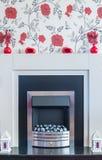 Chrome brandsurround med papper för rosblommavägg över överkanten Royaltyfri Foto