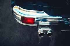The chrome bumper of the retro car. The chrome bumper of the retro car is green with a beautiful exhaust system Royalty Free Stock Images