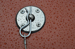 Chrome vehicle bonnet pin. Chrome car bonnet pit fastener with rain droplets on paint work royalty free stock photos