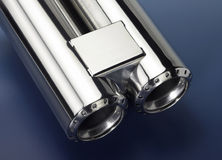 Chrome double exhaust pipe. Studio shot of a chrome double exhaust pipe in dark blue back Stock Images