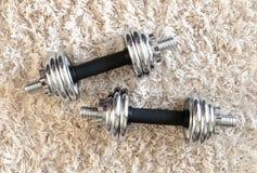 Chrome Dumbbell on white carpet Stock Images