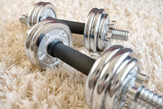 Chrome Dumbbell on white carpet Royalty Free Stock Image