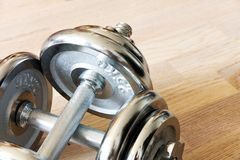 Chrome dumbbells. Chrome dumbbell on a wooden floor, two dumbbells lying one over the other Stock Images