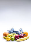 Chrome dumbbells surrounded with healthy fruits measuring tape on a  white background with shadows. Stock Photography