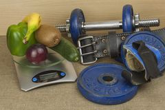 Chrome dumbbells surrounded with healthy fruits and vegetables on a table. Concept of healthy eating and weight loss. Stock Photos