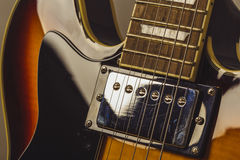 Chrome electric pick up on a dark sunburst electric guitar Royalty Free Stock Image
