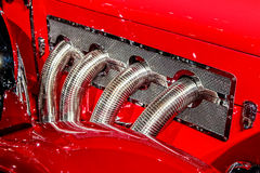 Chrome exhaust detail coming out of the hood of a antique classic red pre-war car. Stock Image