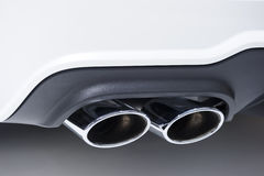 Chrome exhaust pipes. Double chrome exhaust pipe of powerful sport car with white bodywork and grey plastic details Stock Photo