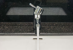 Chrome faucet. In bathroom with black marble background Royalty Free Stock Photos