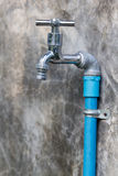 Chrome faucet with blue pipe on wall Stock Image