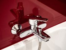 Chrome faucet in with lot of reflection in a red bathroom. Chrome faucet in with lot of reflection in a red reconstructed bathroom Stock Photography
