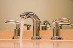 Chrome faucet in luxury bathroom. Close up of shiny chrome faucet in modern luxury bathroom Stock Image