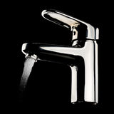 Chrome faucet. Modern chrome faucet with flowing water on black background Royalty Free Stock Image