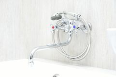 Chrome faucet with showerhead. Chrome faucet in bathroom with separate taps and showerhead Royalty Free Stock Image