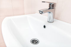 Chrome faucet in the wash basin. Chrome faucet in the ceramic wash basin in the bathroom with a beige tile on wall Royalty Free Stock Photo