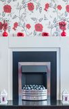 Chrome fire surround with rose flower wall paper over the top. Black and white fire surround with ornamental lanterns at the sides, flower vases on the top of royalty free stock photo