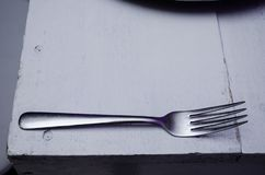Chrome fork on a white wooden table, beautiful background for decorating food presentations stock photography