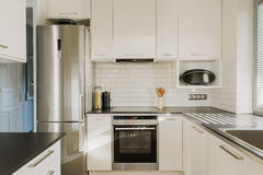 Chrome fridge in white kitchen. New chrome fridge in luxury white kitchen stock photography