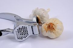 Chrome garlic press and garlic bulbs. Stock Images
