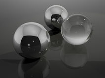 Chrome and Glass Balls. Chrome and glass spheres in a studio photography box with reflections and refractions.  Neutral colour and interesting reflections when Royalty Free Stock Image