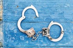 Chrome-handcuffs op blauwe houten achtergrond royalty-vrije stock afbeeldingen