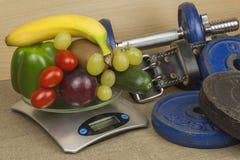 Chrome hantlar som omges med sunda frukter och grönsaker på en tabell Begrepp av sund äta och viktförlust Royaltyfri Foto
