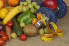 Chrome hantlar som omges med sunda frukter och grönsaker på en tabell Begrepp av sund äta och viktförlust Royaltyfri Fotografi