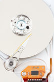 Chrome hard drive with orange ribbon. Chrome - sliver hard drive with orange circuit board and ribbon. top down closeup view royalty free stock photo