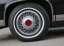 Chrome hjul med silvrig eker och ett nytt gummi på en svarta skinande Cadillac royaltyfri bild