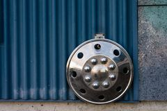 Chrome hubcap against blue wall with texture Stock Photo