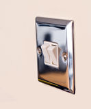 Chrome light switch. On a magnolia wall Royalty Free Stock Image